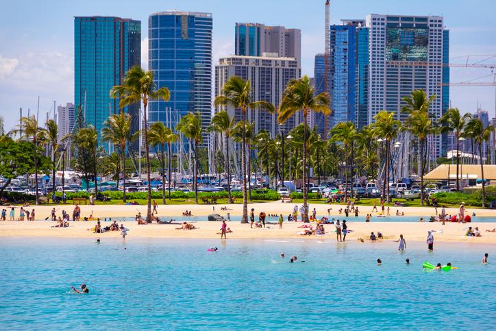 Tourists Swimming, Sunbathing on Waikiki Beach, Honolulu, Oahu, Hawaii.