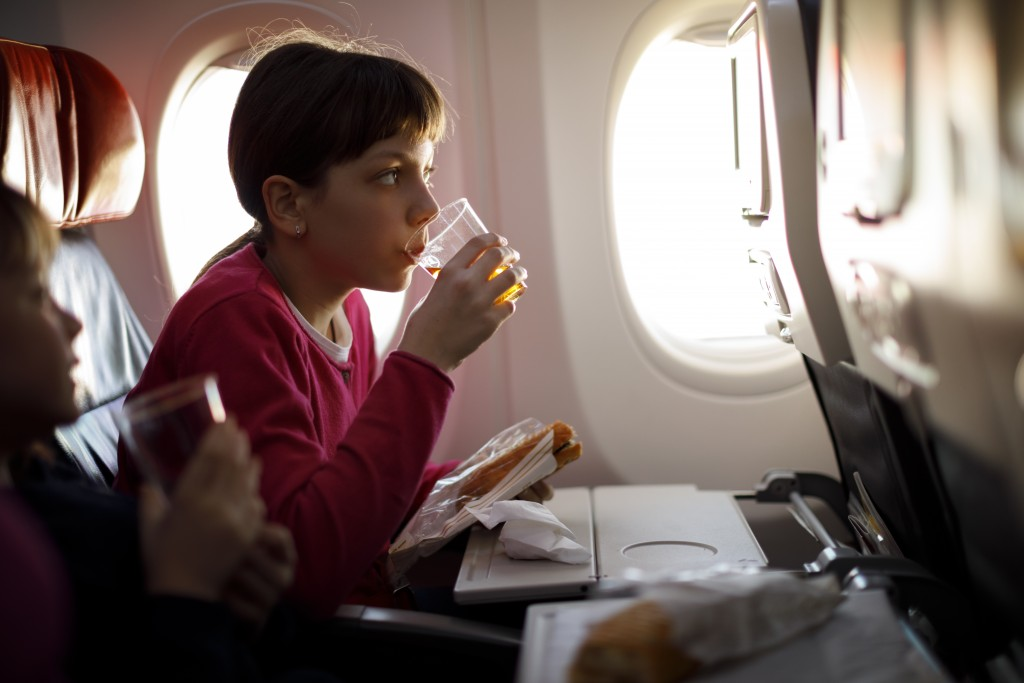 Young girls having meal on board of plane
