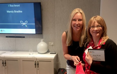 TravelManagers national business partnership manager, Suzanne Laister, presents Personal Travel Manager, Mandy Bradtke, with her five year milestone award