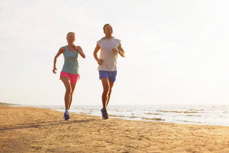 Happy fitness couple running on the beach