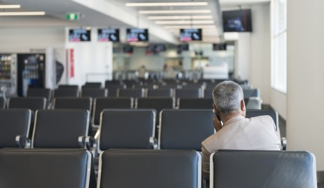 Sydney, Australia - November 18, 2015: An unrecognisable male person is waiting for a flight in an empty gate at Sydney Kingsford Smith Airport departures terminal. He is the only person at the gate.