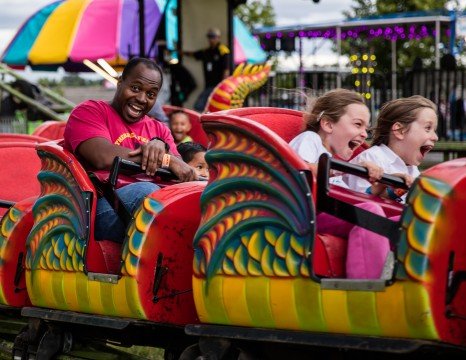 Anderson, California, USA- June 17, 2016: County fair goers enjoying a ride in the shape of a dragon at the Shasta County Fair in northern California.
