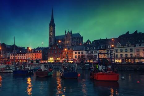 Port, houses, restaurants, shops, bars, pubs and Cathedral at night in Cobh, Ireland. Famous tourist seaport town and popular touristic destination