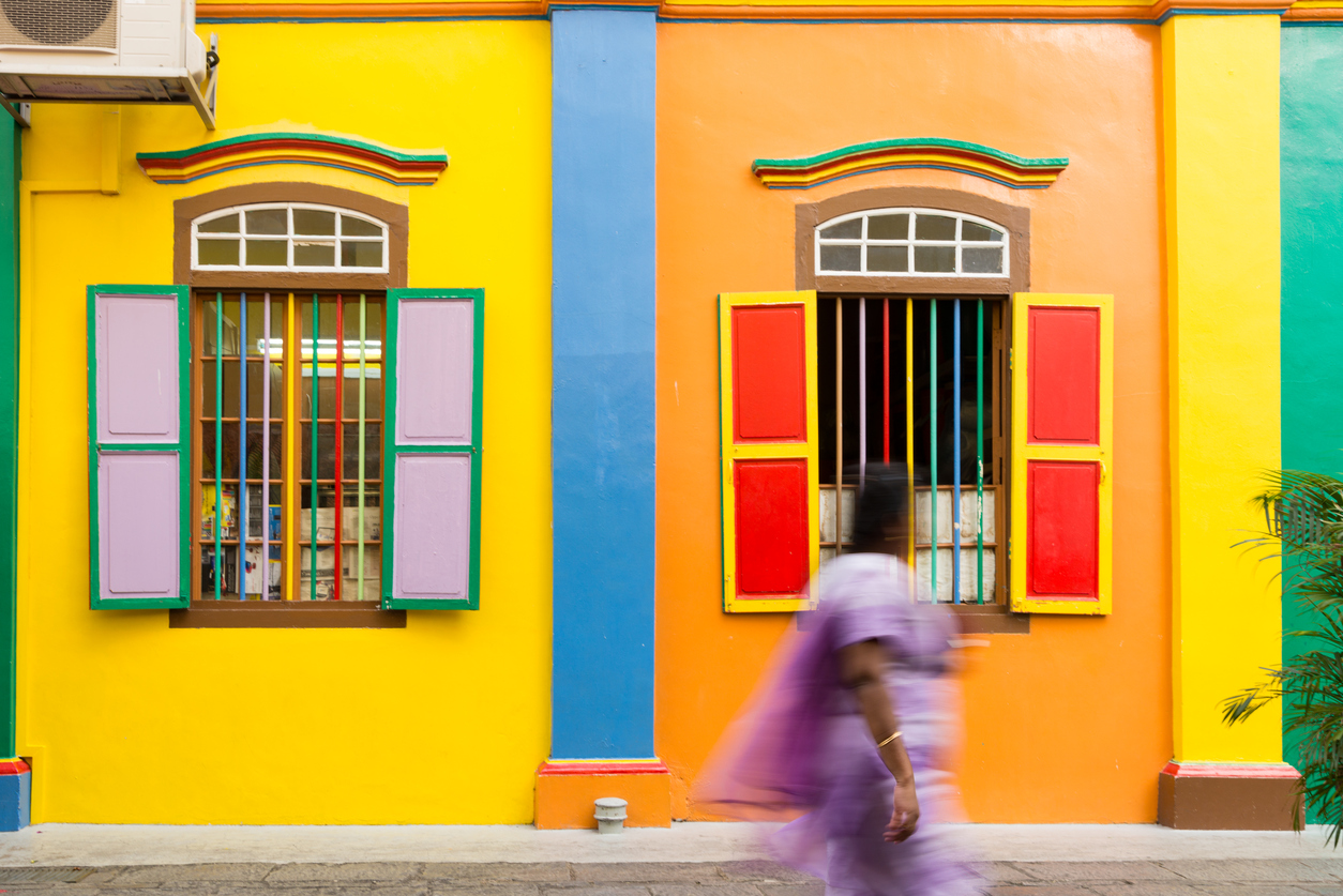 Singapore, Singapore - August 23, 2014: Colourful facade of a building in Little India in Singapore. An Indian lady can be seen walking by (motion blur). The image was taken mid-day.