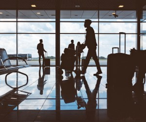 Silhouette of people with luggage waiting at airport lounge