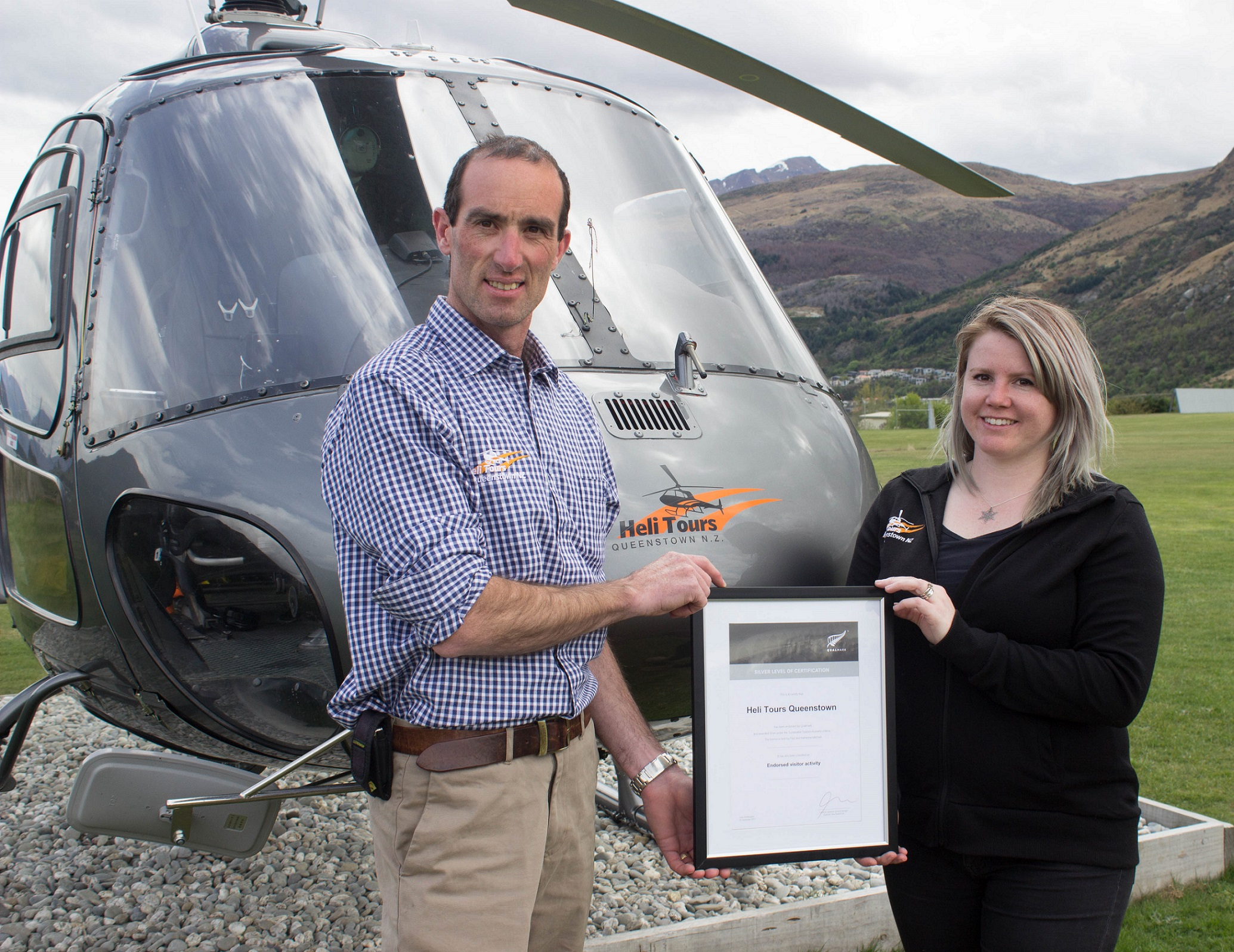 Heli Tours owner Paul Mitchell and Base Manager Jaime Flemming celebrate their Qualmark Silver award