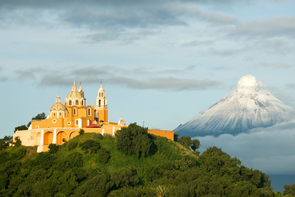 View of Popocatepetl volcano, with the church of Nuestra Señora de los Remedios at the front. City of Cholula, Mexico.