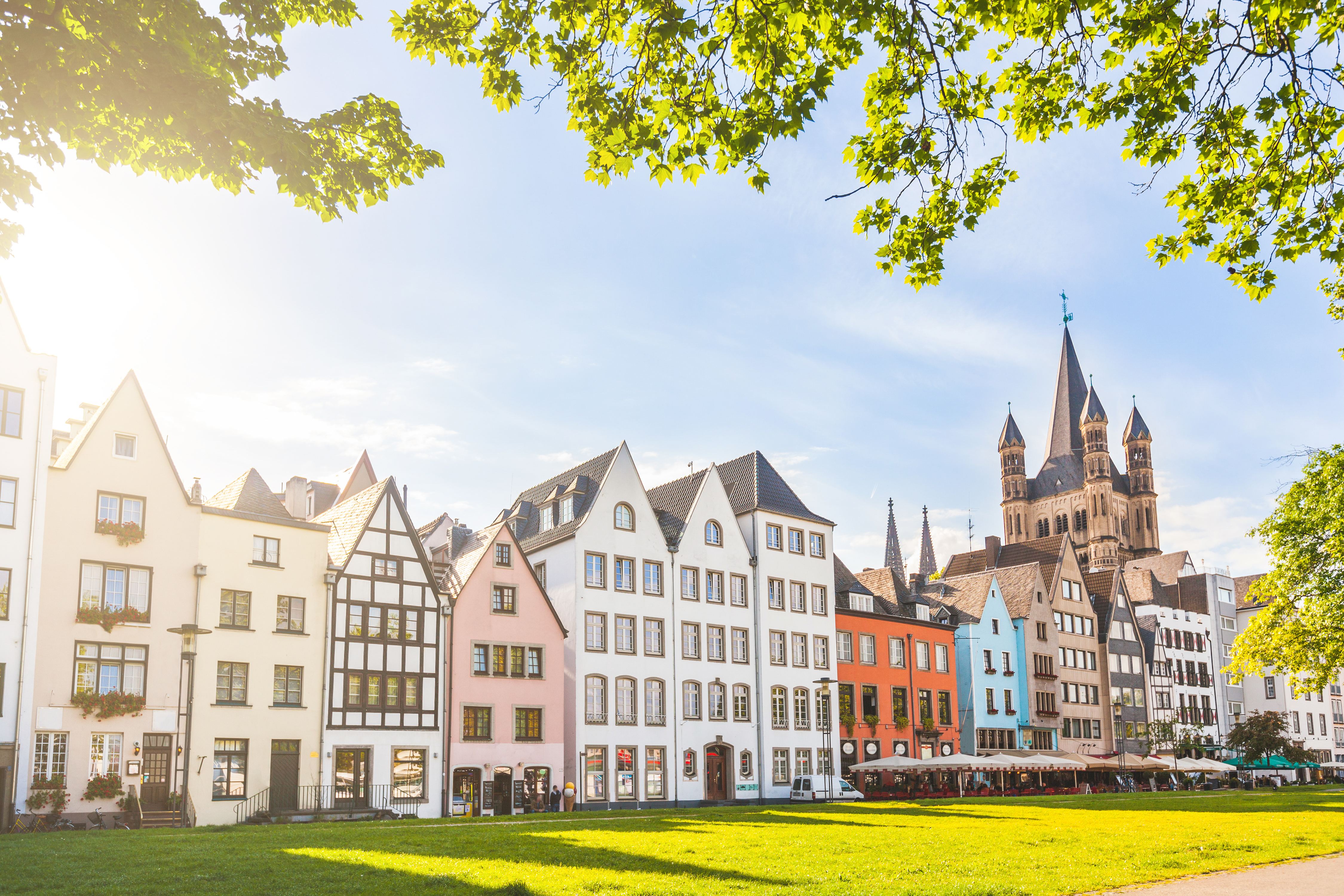 Houses and park in Cologne, Germany. Many of them are colourful, they are facing a public park with green grass and some trees. There is a bell tower on background. Travel and architecture concepts.