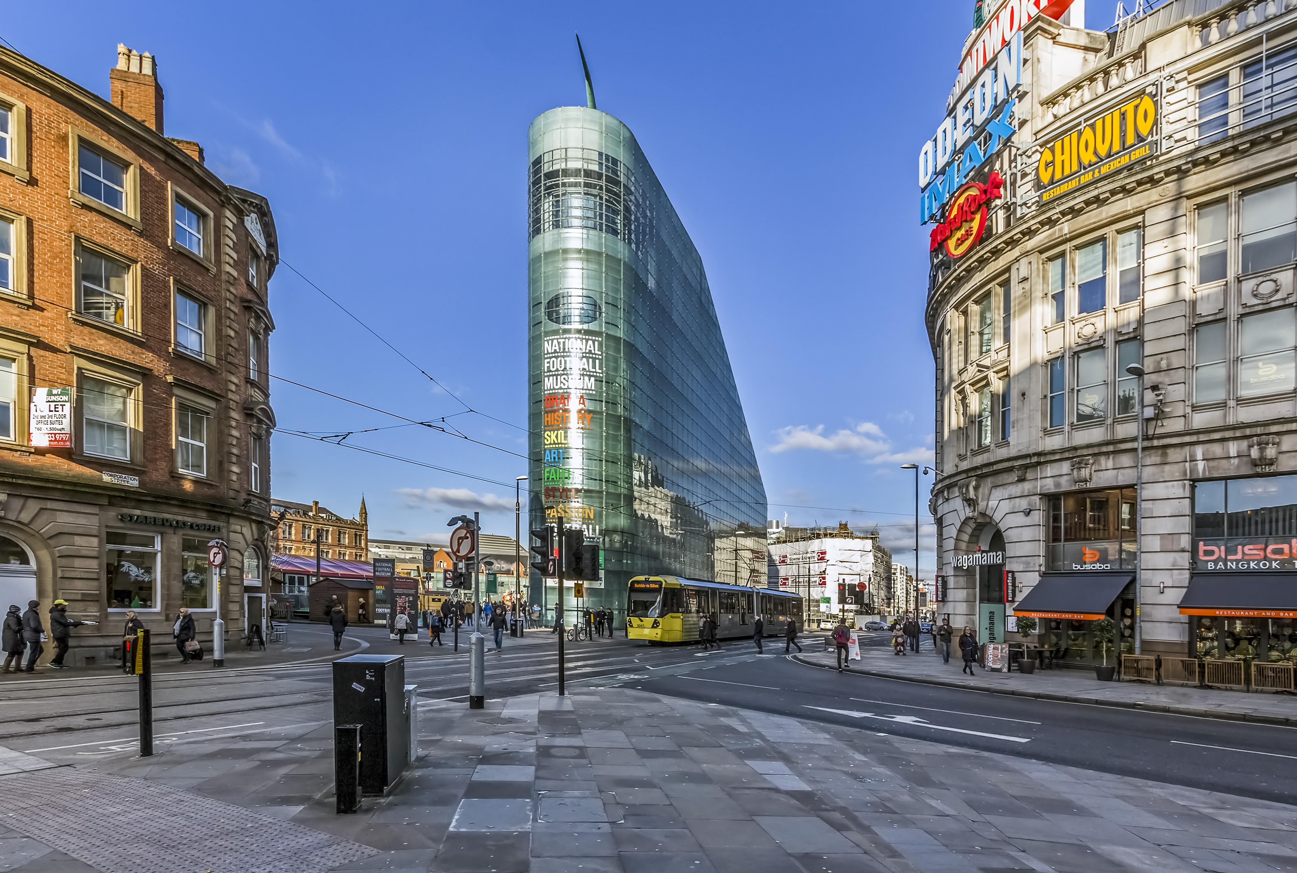 Manchester, UK - November 24, 2016: View of Manchester city center. Tall buildings an be seen on either side of the road and a tram can be seen passing. People can be seen walking on the pavements.