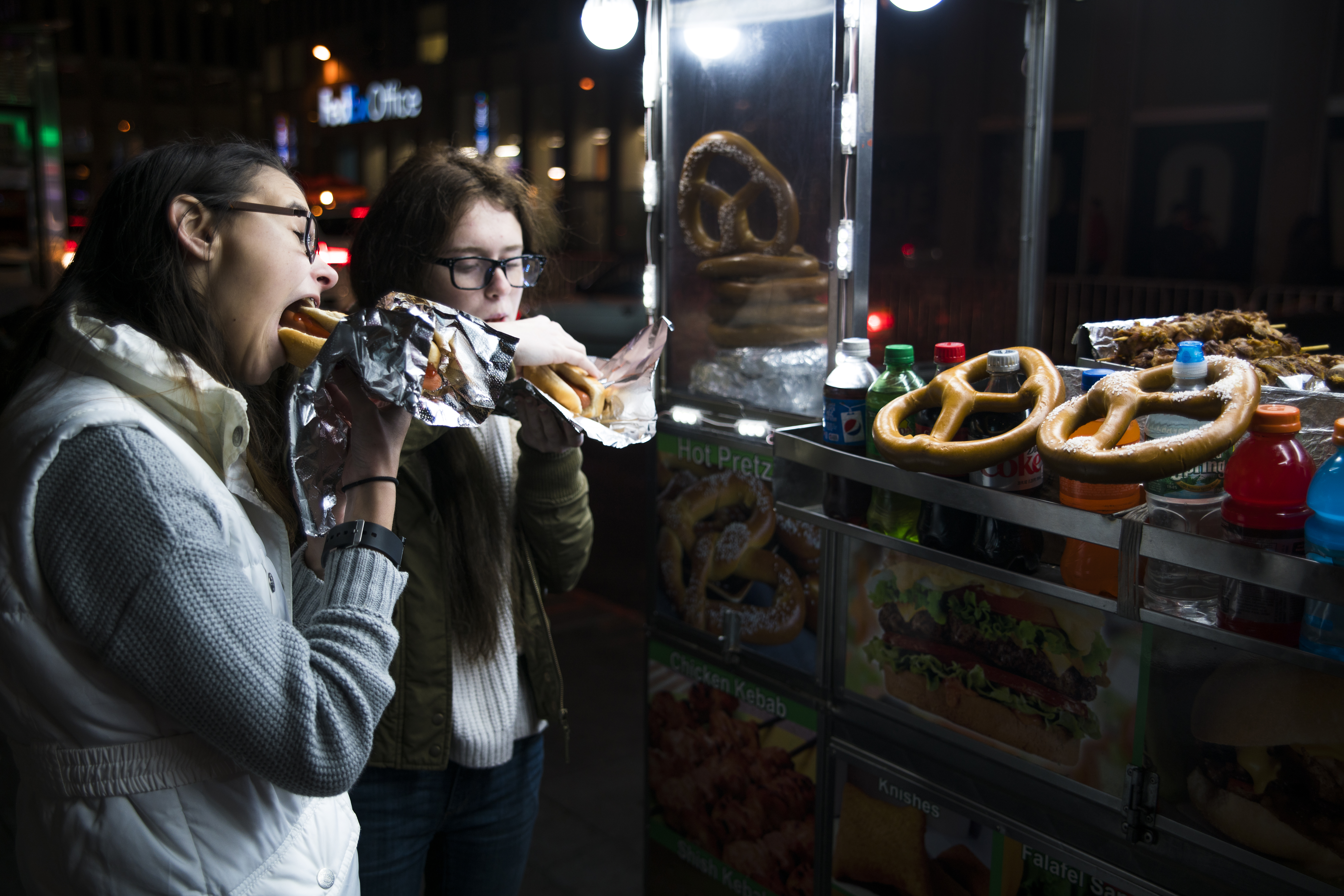 Two teenager girls, sisters, eats fastfood on the street