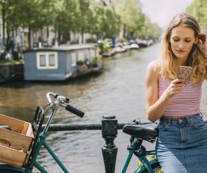 Young woman resting against a bicycle and railing at the canal while she uses her mobile telephone