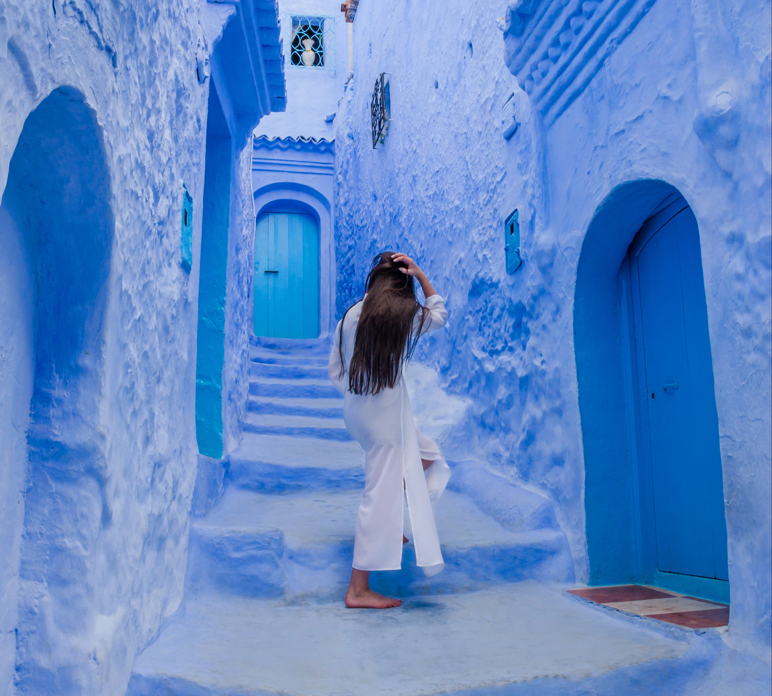 Beautiful girl in a white dress against a blue city Chefchaouen, Morocco