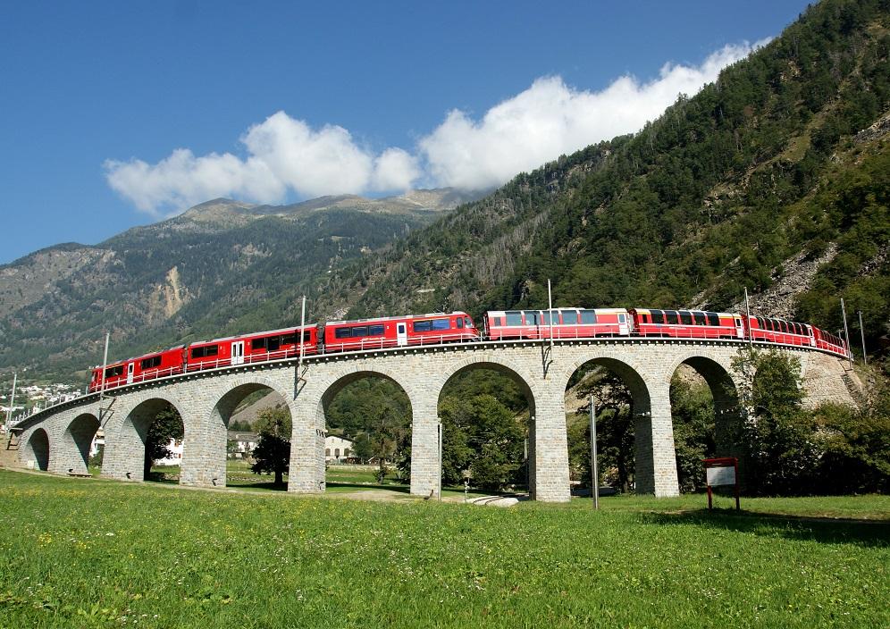 Rhaetische Bahn/RhB - Bernina Express - Bernina Express auf dem bekannten Kreisviadukt bei Brusio. Eine Fahrt von den Gletschern zu den Palmen. Rhaetian Railway/RhB - Bernina Express - The Bernina Express crosses the famous Brusio Circular Viaduct. Ferrovia retica/FR - Bernina Express - Il Bernina Express sul noto viadotto circolare di Brusio. Un viaggio dai ghiacciai alle palme. Copyright by Rhaetische Bahn By-line: swiss-image.ch/Giorgio Murbach