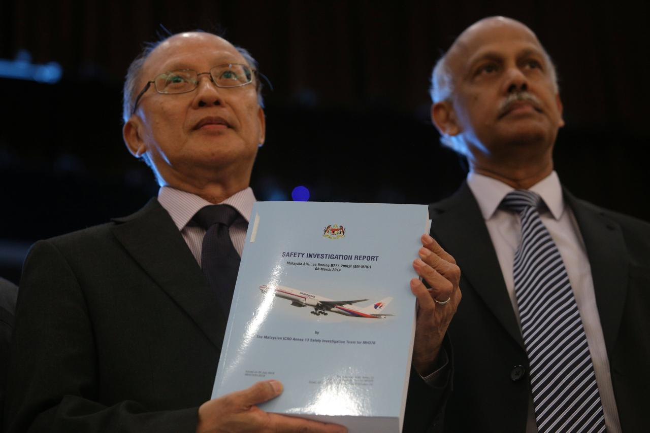 MH370 safety investigator-in-charge Kok Soo Chon shows the MH370 safety investigation report booklet to the media after a news conference in Putrajaya, Malaysia July 30, 2018. REUTERS/Sadiq Asyraf