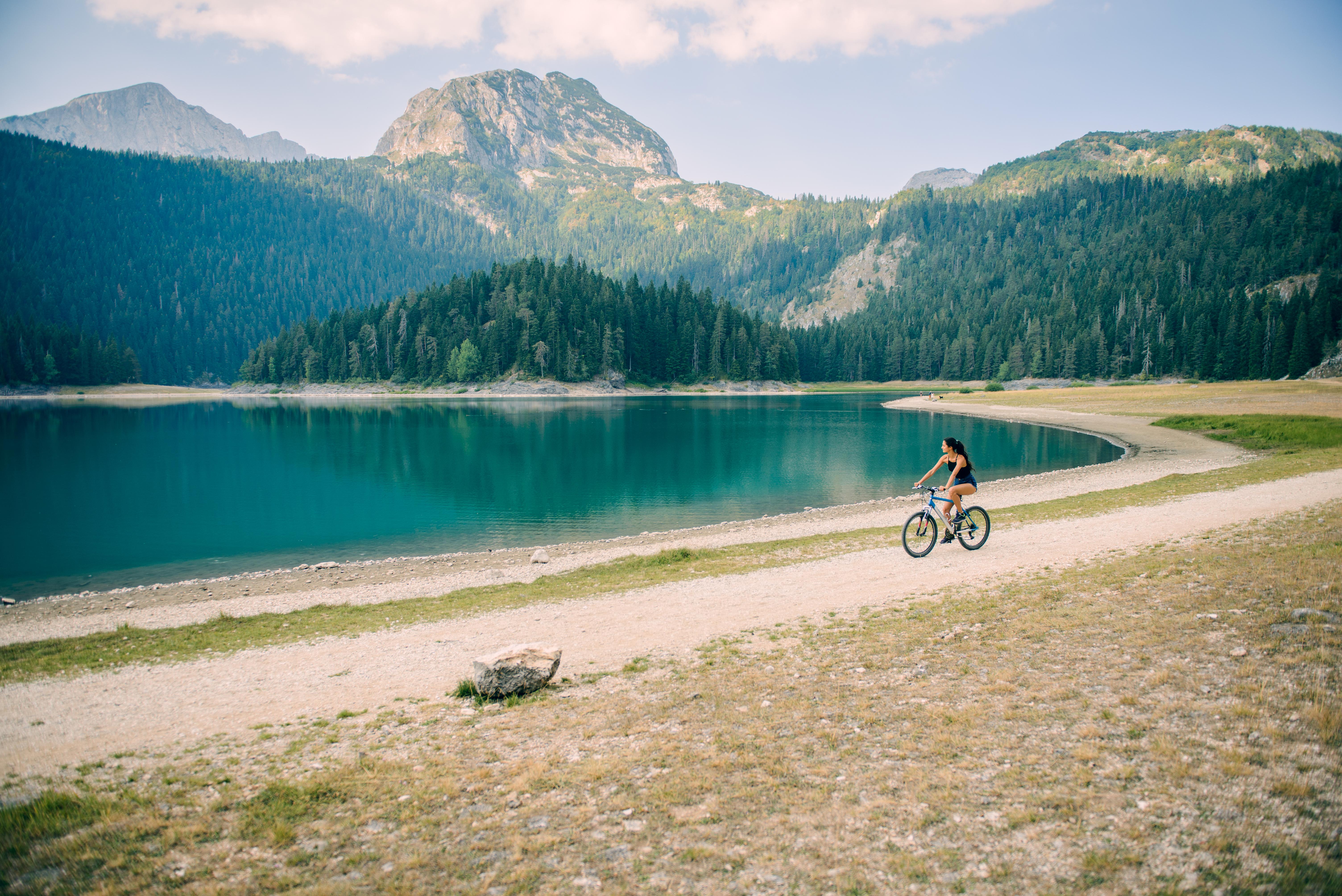 Woman riding a bike by the lake.