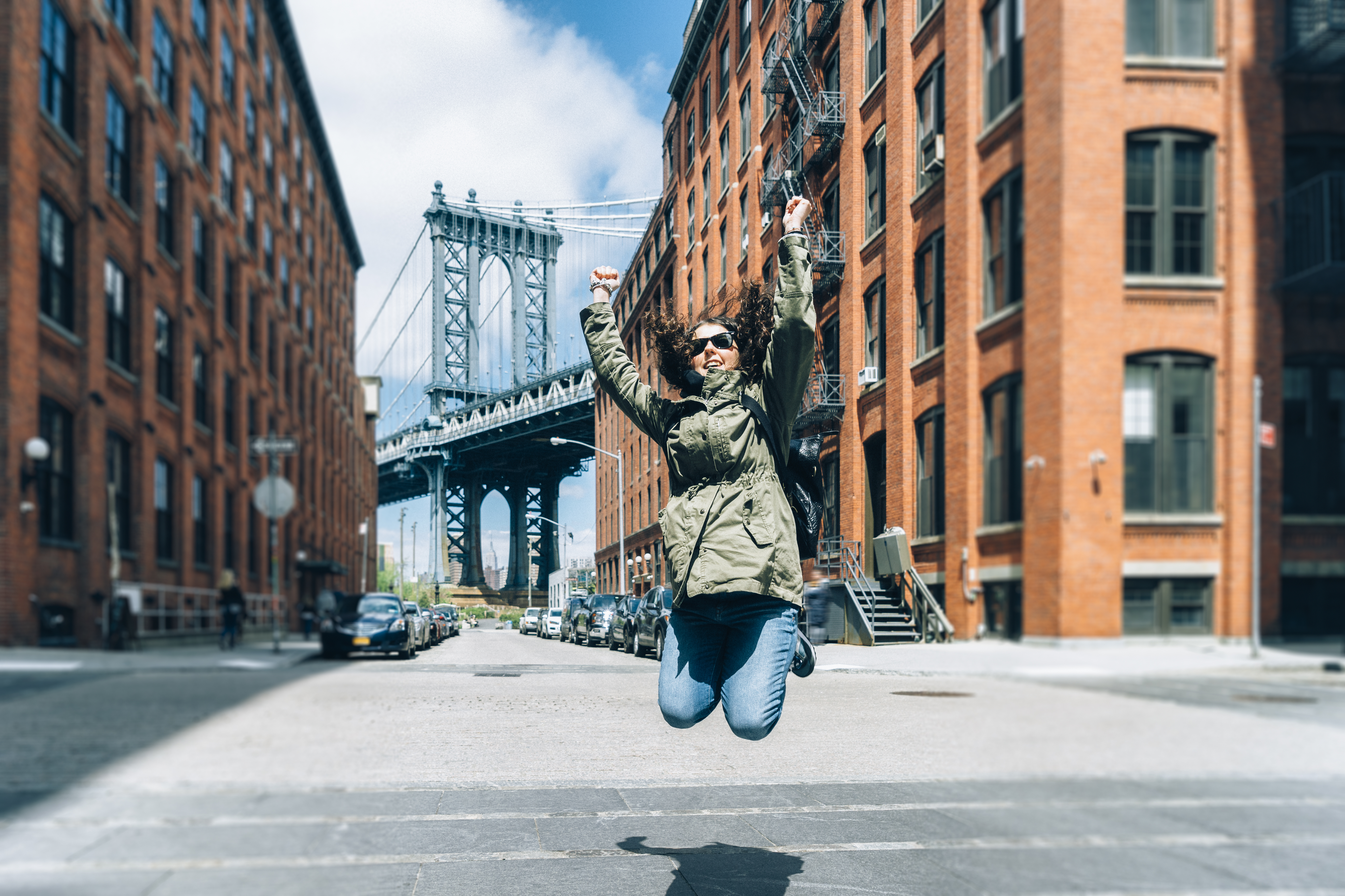 Happy Young Woman Jumping Near Manhattan Bridge in New York