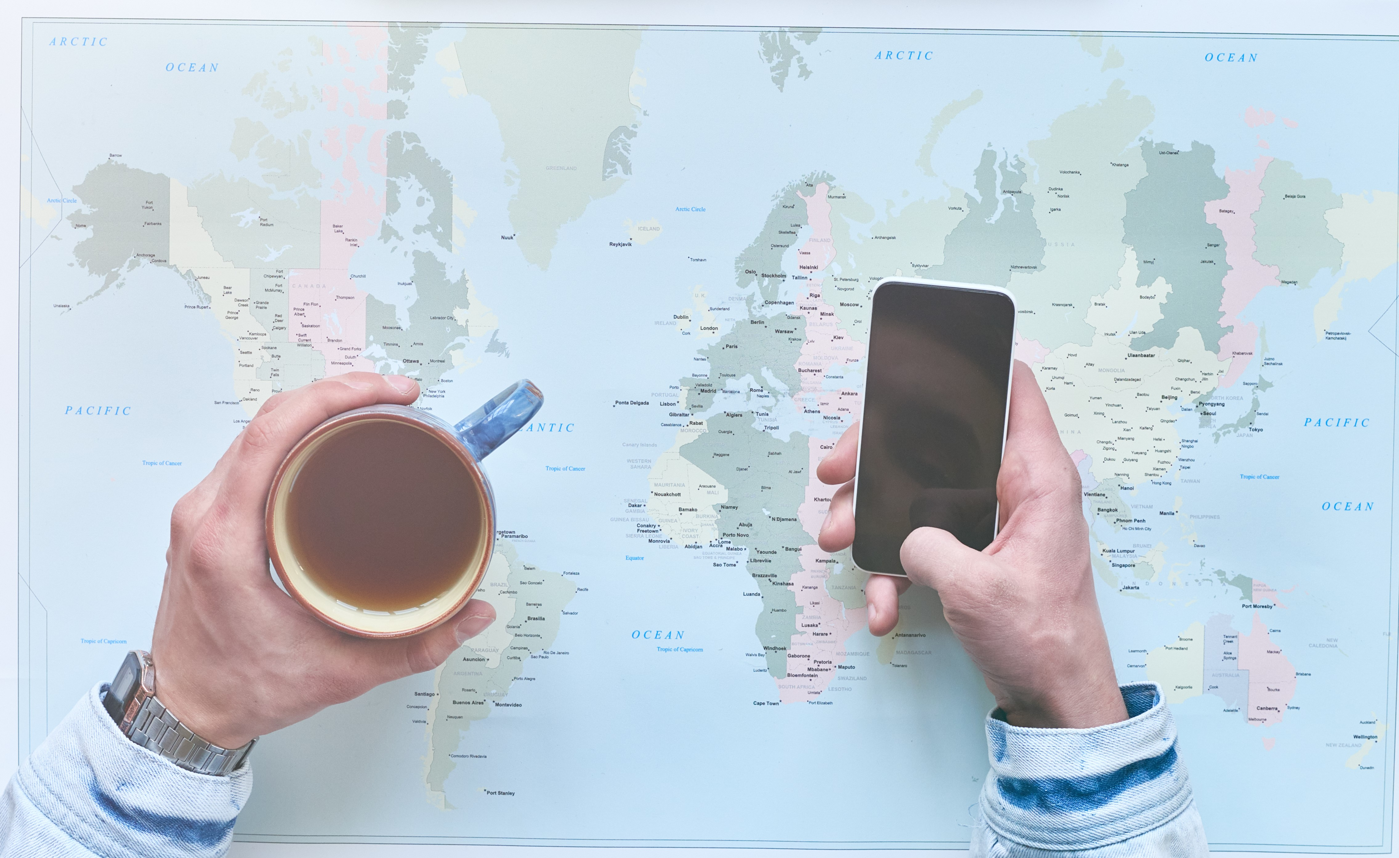 Directly above view of man using smartphone and drinking tea at desk with world map