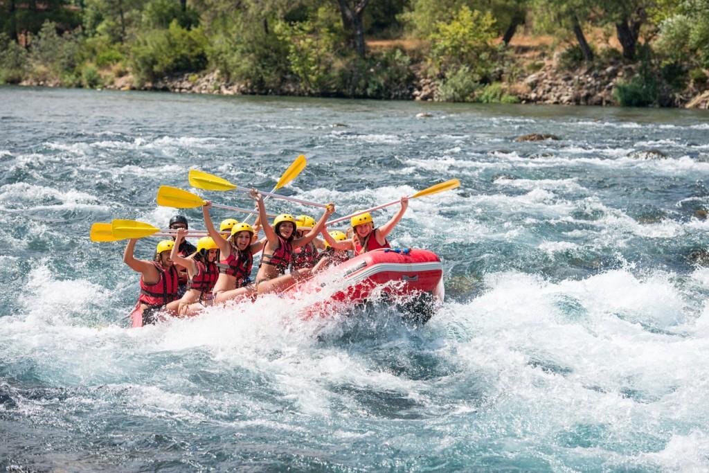 Group of people white water rafting. The raft goes through a big rapid on Koprulu Canyon near Antalya, Turkey