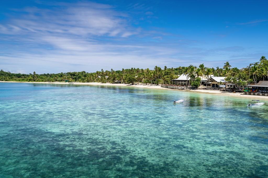 Mana Island, Fiji - November 3, 2016: Mana Island Beach in the Mamanuca Islands under blue summer sky. Mamanuca Islands, Fiji, Melanesia, South Pacific Ocean.