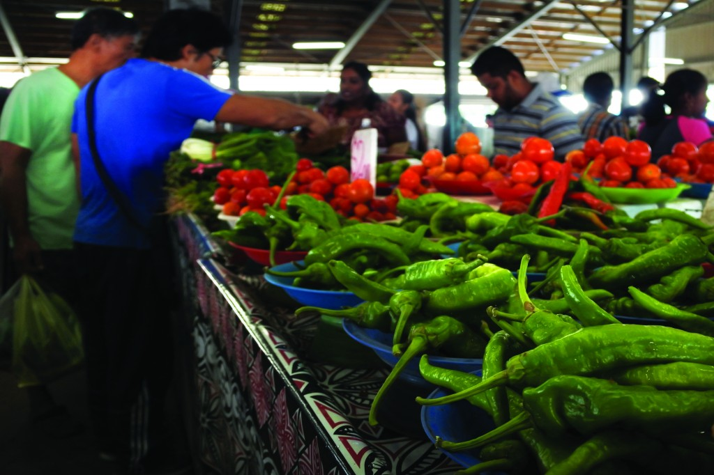 Customers shop for fresh vegetables and hot green chilies in a local market in Fiji