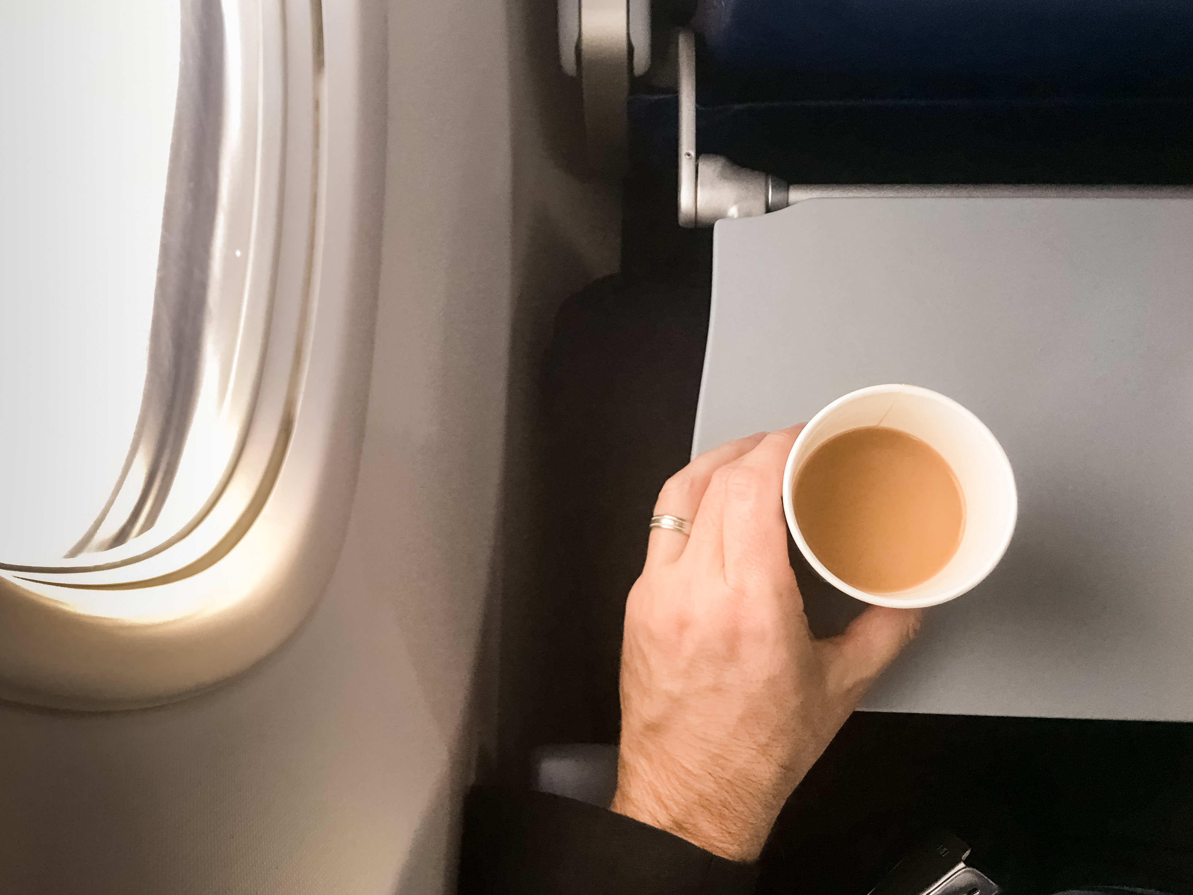 Male passenger holding a cup of coffee in aircraft