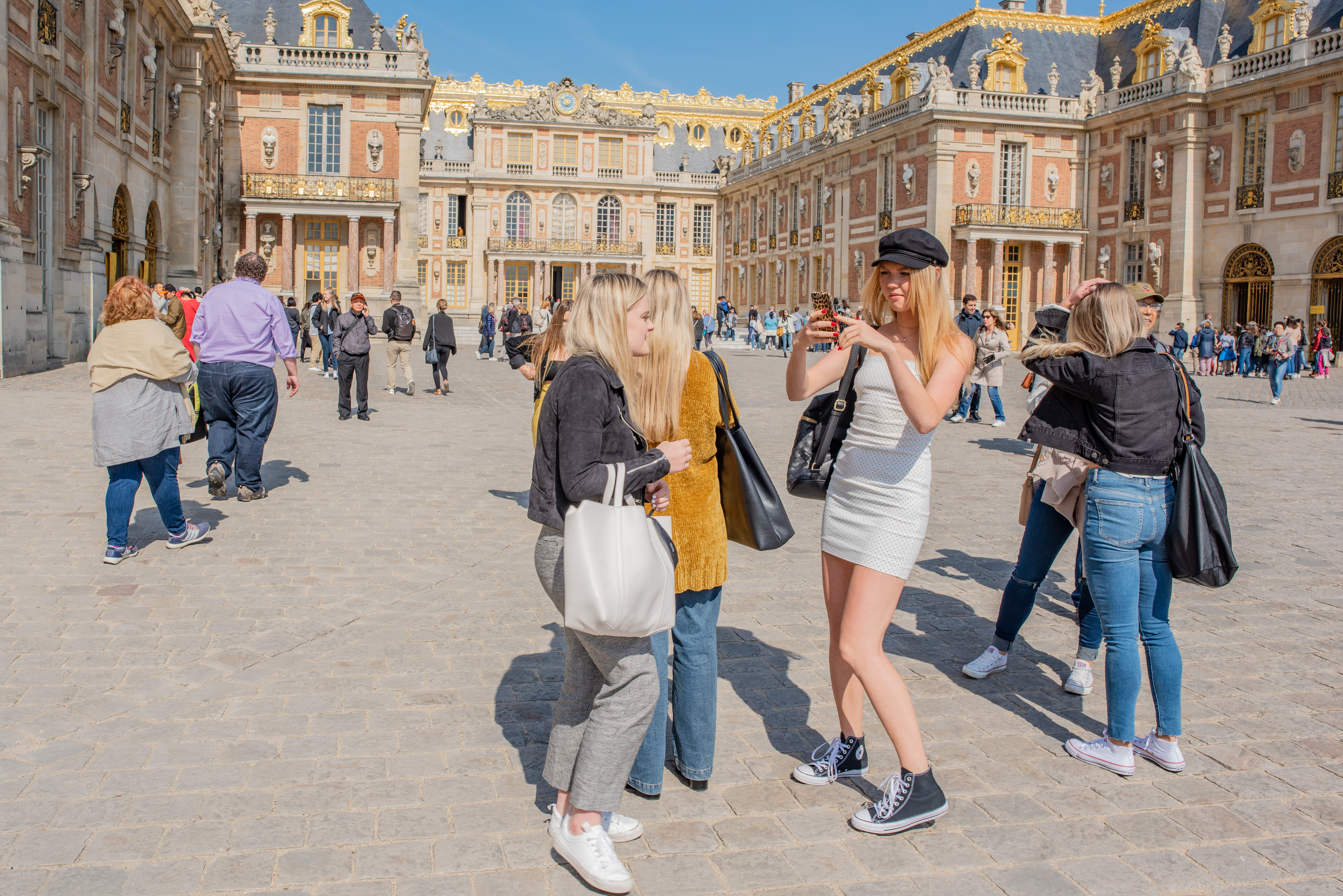 Young women take selfies outside the Palace at Versailles.