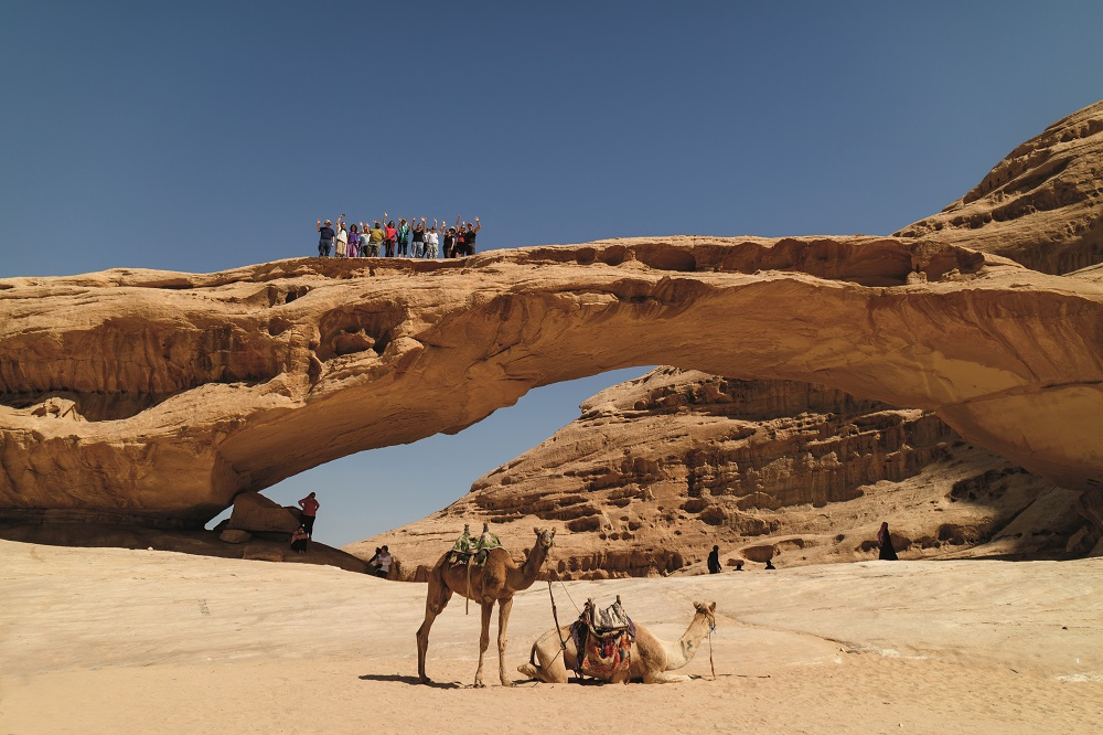 Group on top of arch in Wadi Rum Desert