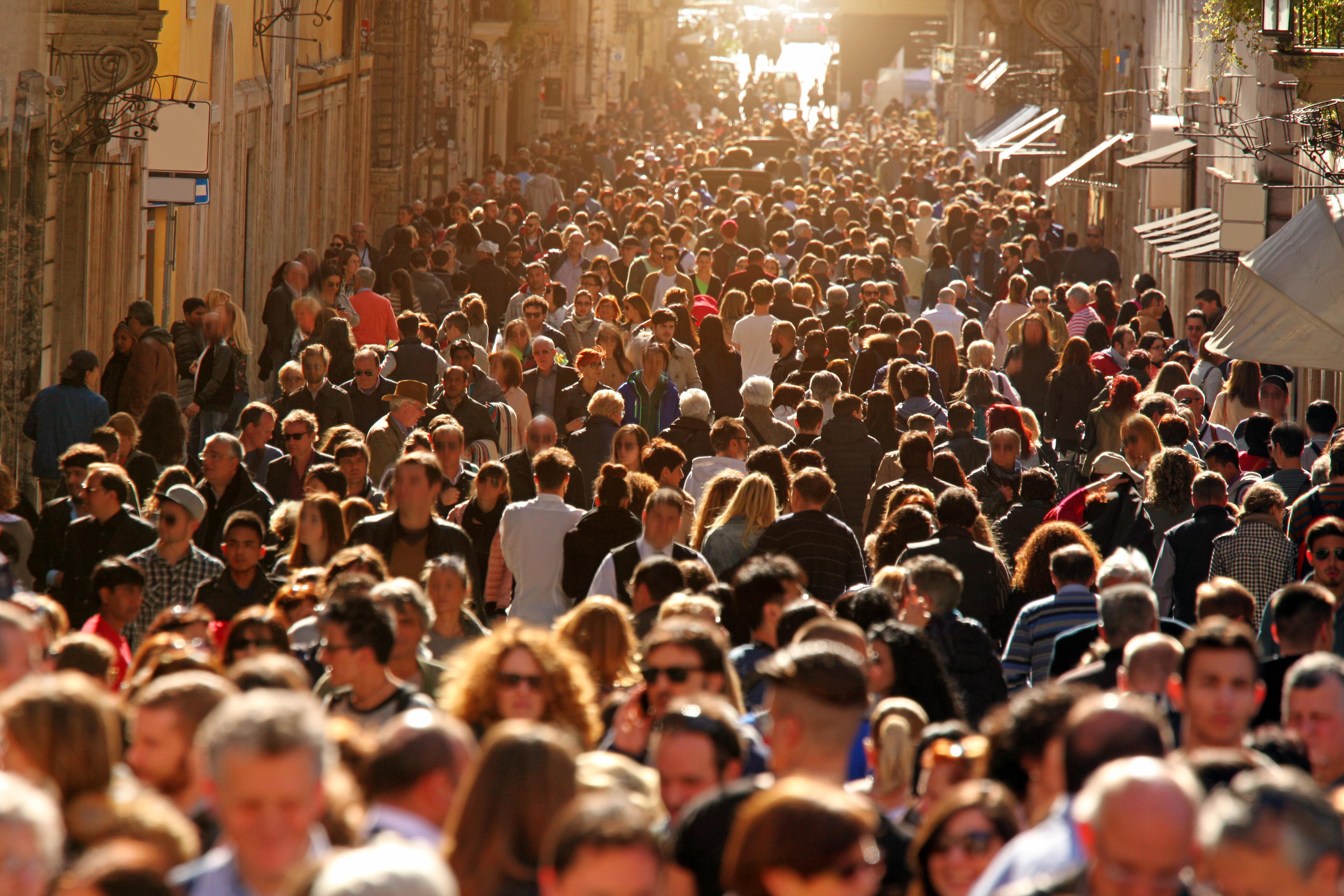 Crowd of people walking on street in downtown Rome, sunlight