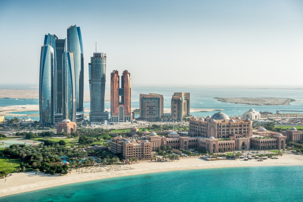 Helicopter point of view of sea and skyscrapers in Corniche bay in Abu Dhabi, UAE. Turquoise water and blue sky combined with building exterior.