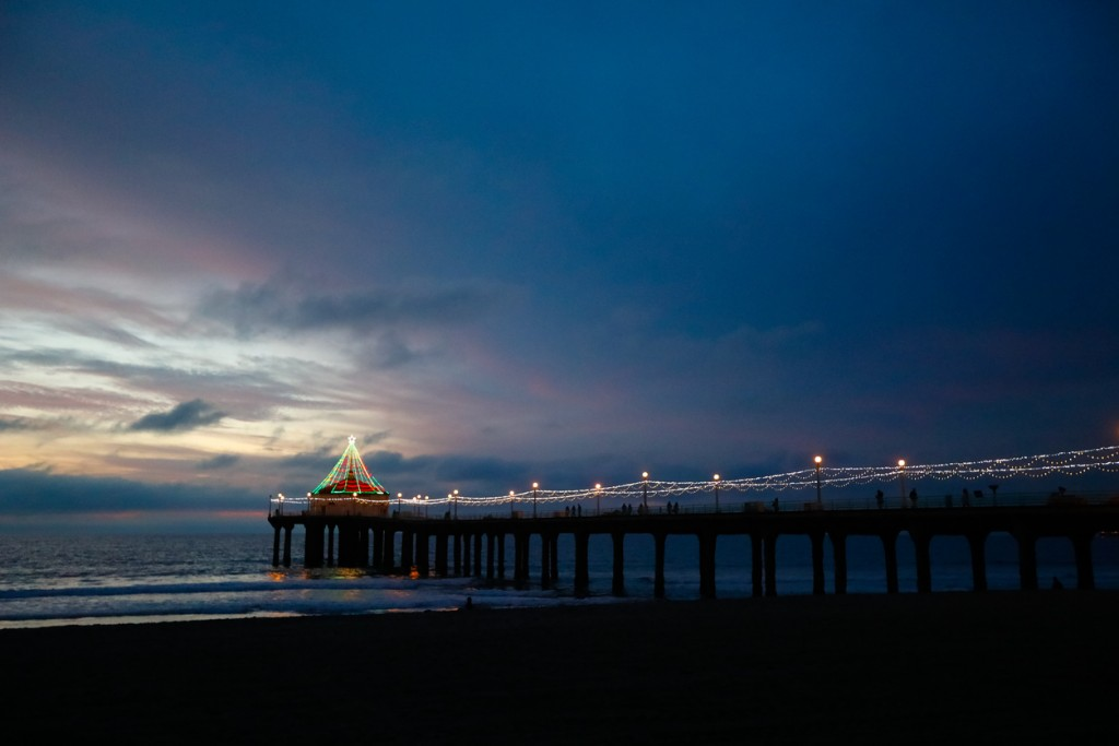 The beautiful and iconic Manhattan Beach Pier at dusk overlooking the Pacific Ocean. The dramatic skies cast a colorful glow. The lights are installed by the city for a holiday vibe.