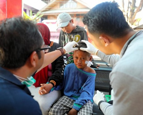 PALU, INDONESIA - OCTOBER 01: (CHINA OUT, SOUTH KOREA OUT) A 7-year-old injured boy, whose mother and young sister remain missing, receives treatment after strong earthquake on October 1, 2018 in Palu, Indonesia. Over 844 people have been confirmed dead after a tsunami triggered by a magnitude 7.5 earthquake slammed into Indonesia's coastline on the island of Sulawesi, causing thousands of homes to collapse, along with hospitals, hotels and shopping centers. Emergency services fear that the death toll could rise into the thousands as rescue teams made contact with the nearby cities of Donggala and Mamuju and strong aftershocks continue to rock the city. (Photo by The Asahi Shimbun/The Asahi Shimbun via Getty Images)