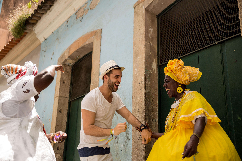 """Tourist dancing with local Brazilian woman """"Baiana"""" in Pelourinho, Salvador, Bahia, Brazil"""