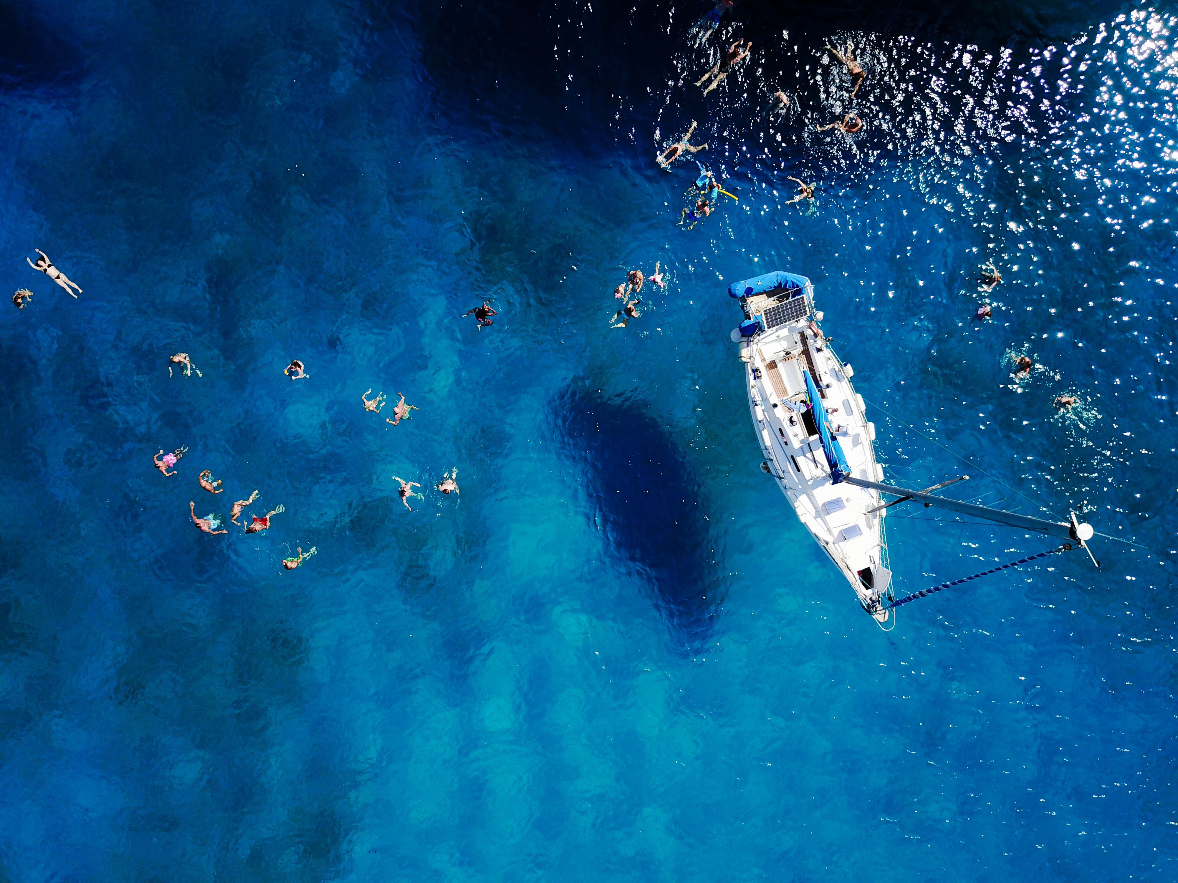 Aerial shot of beautiful blue lagoon at hot summer day with sail