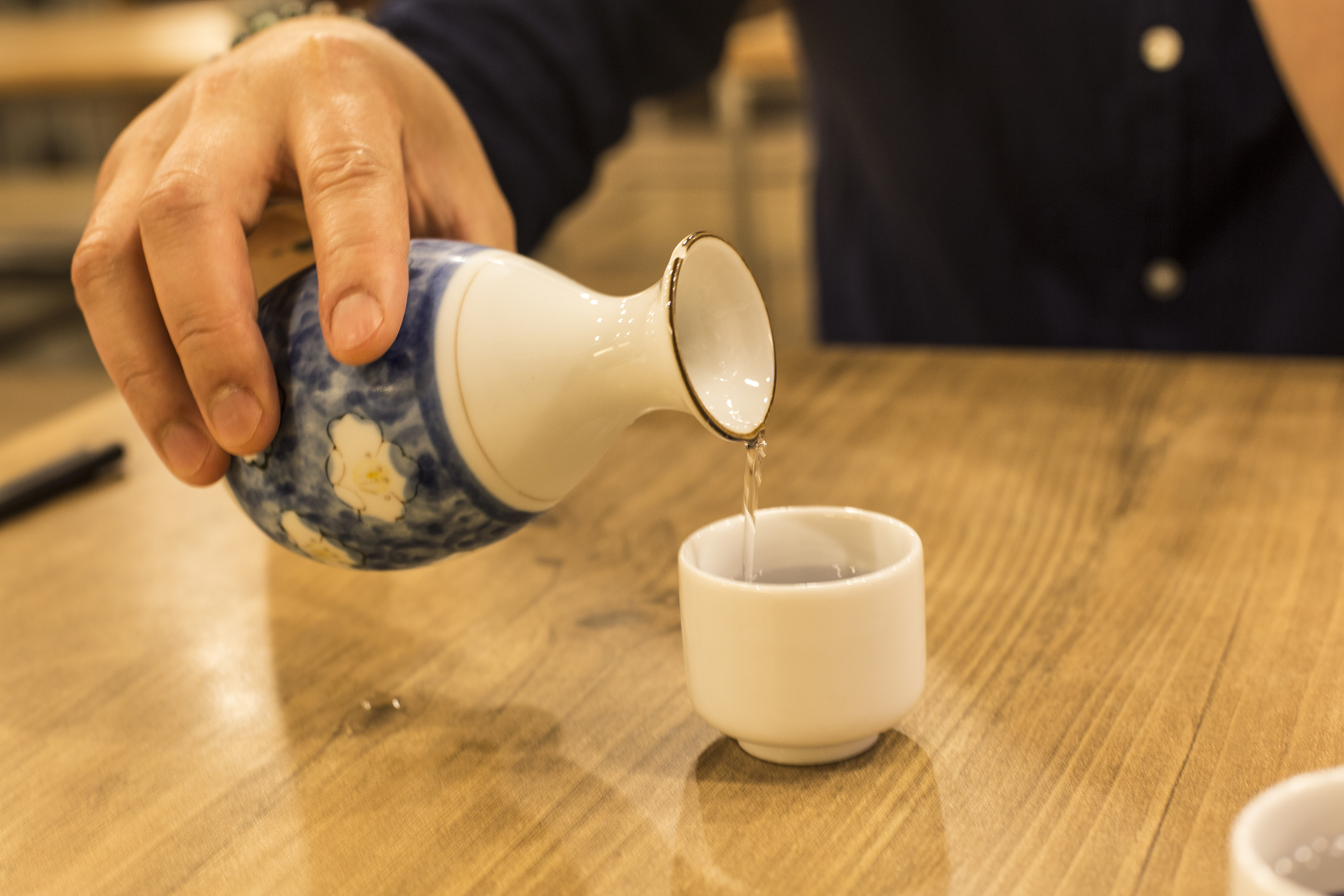 Prepared to drink sake on wood table(sake bottle and cups)