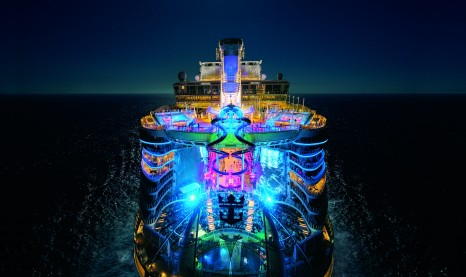 HM, Harmony of the Seas, OOH, night, nighttime drone shot, aerial of ship, aft, rear view, colorful lights, Ultimate Abyss in center, top pool decks,