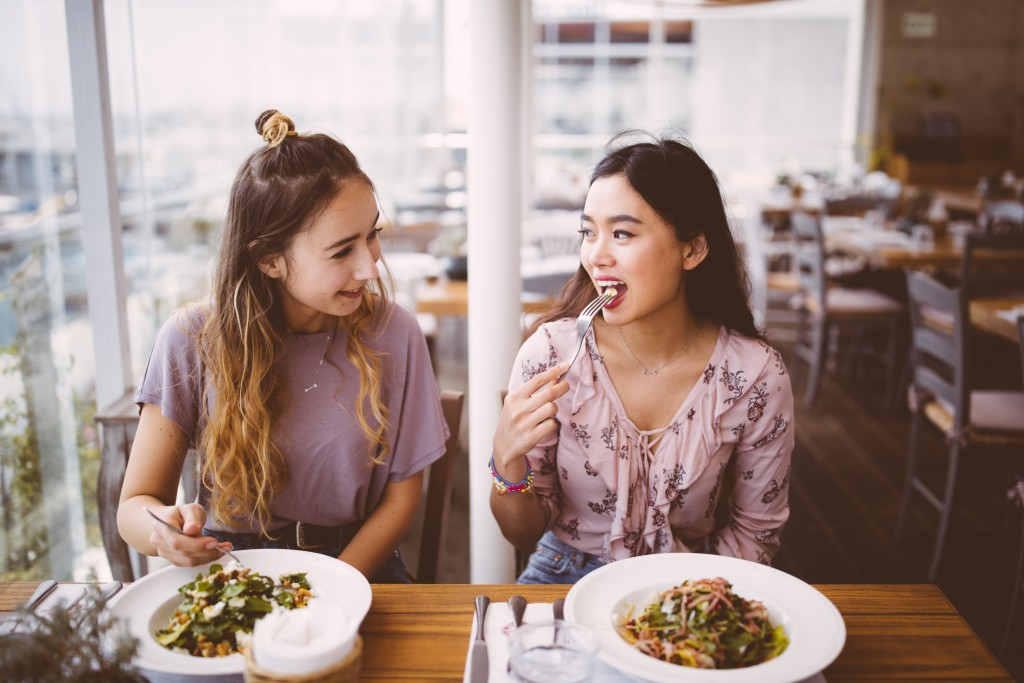 Multi-ethnic female hipster friends having lunch together at Italian restaurant