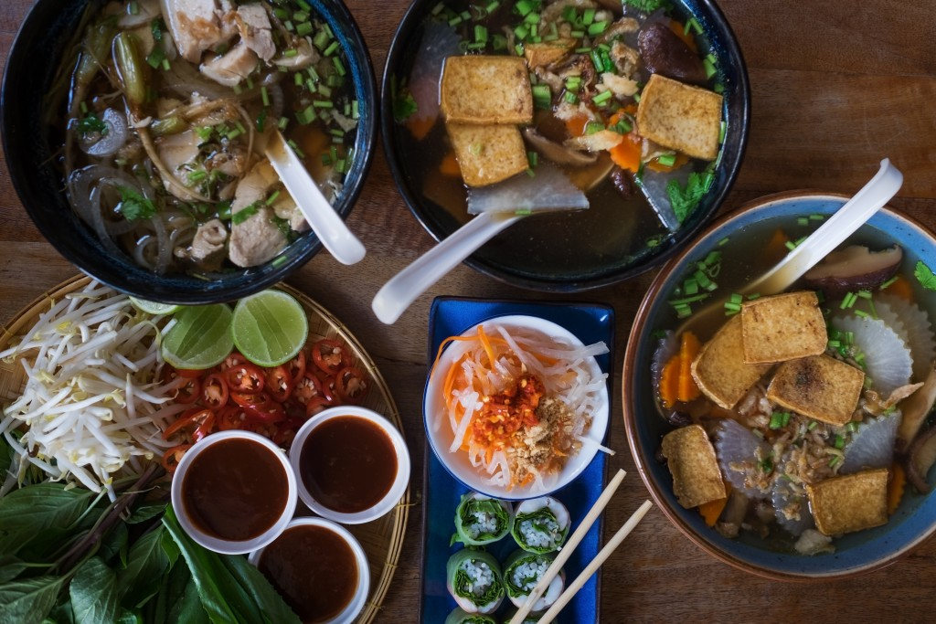 Traditional Vietnamese food. Soups, rolls and fresh herbs. Plates on a wooden surface.