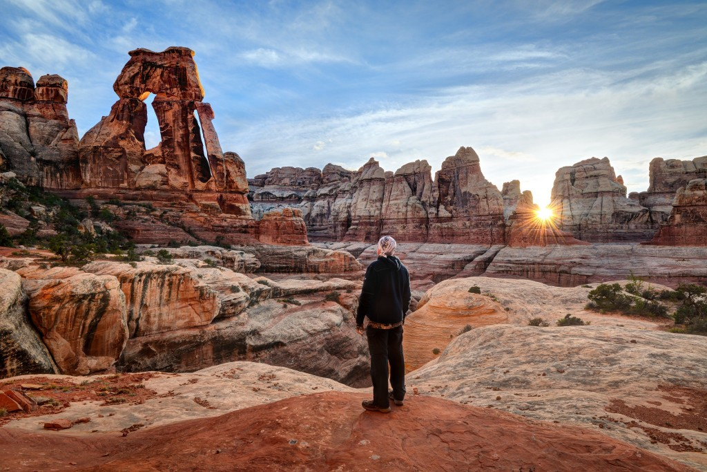 Man Looking up at Druid Arch in Canyonlands National Park
