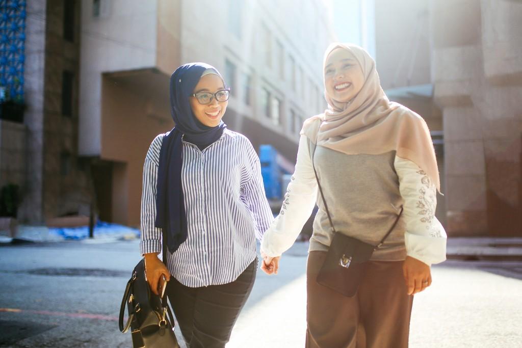 Two beautiful Malaysian women talking on the streets of Kuala Lumpur, Malaysia