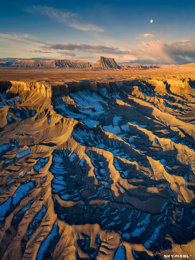 """Image by: 梦中画. """"This image was taken by DJI P4P in Utah. The texture of the badlands looked carving paint from air. The snow in the shadow gave some cool colours to this paint."""""""