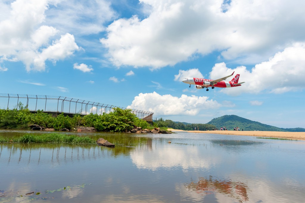 Unidentified tourists at Mai Khao beach with commercial aircraft landing at Phuket International Airport