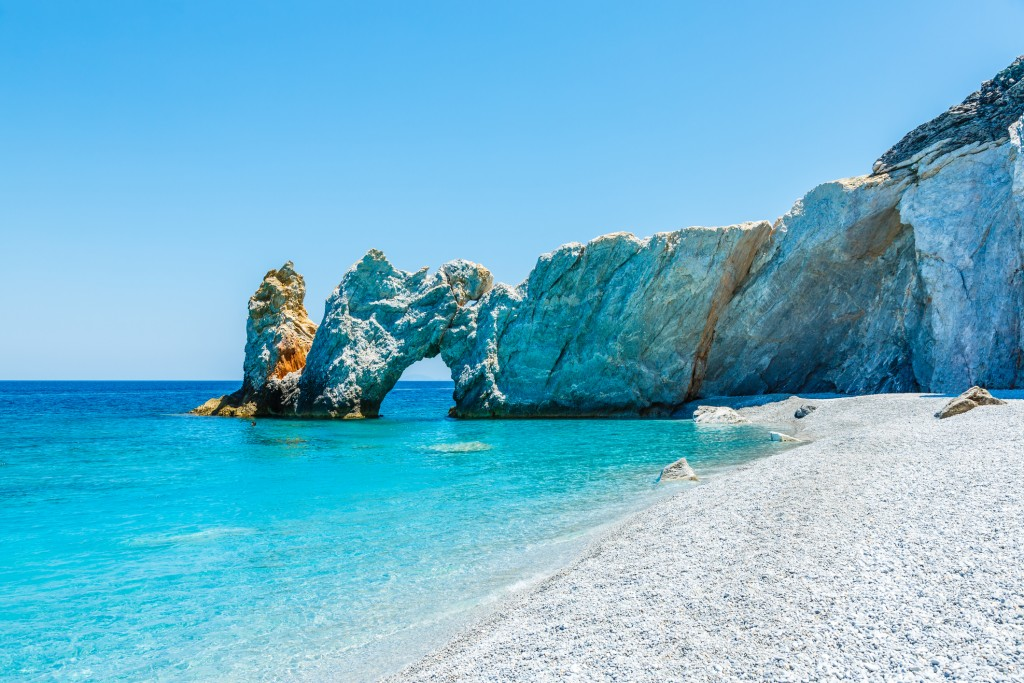 The famous hole in the rock formation at Lalaria beach, Skiathios island, Greece.