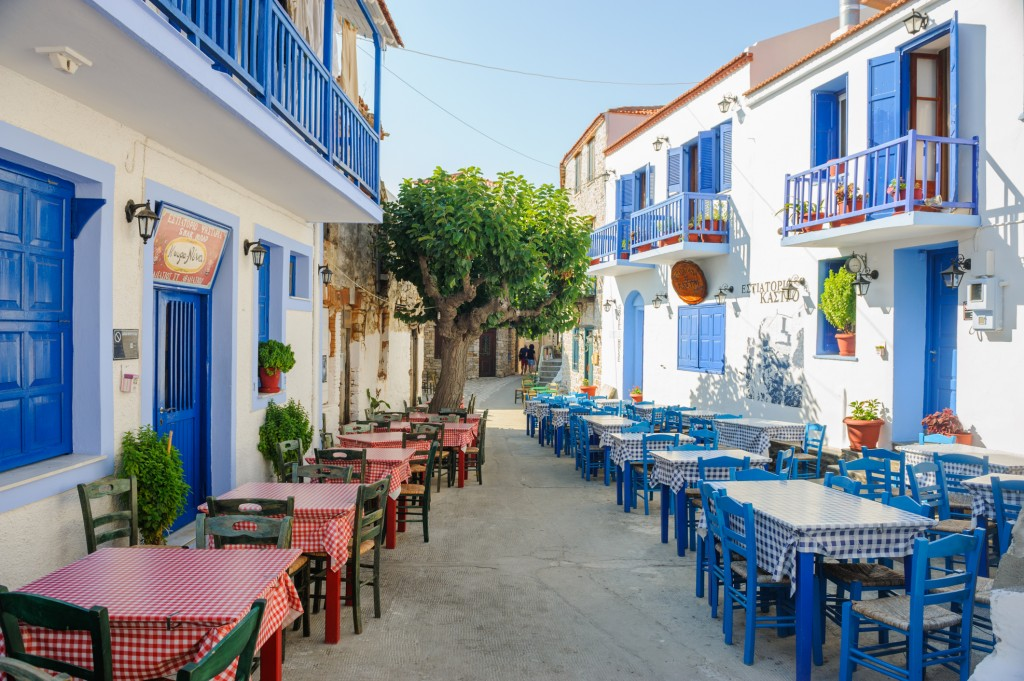 Alonissos, Greece - September 3, 2015: Typical Greece square in an ancient town Alonissos with typical exterior with blue doors and blue fence. Old town Alonissos, tourist spot with ancient houses transformed into restaurants