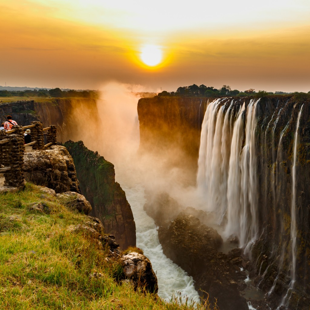 Victoria falls sunset with orange sun and tourists