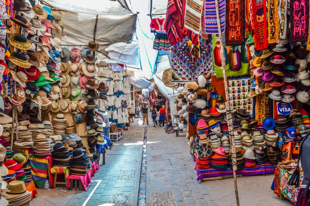 Pisac, Peru - August 24, 2014: Typical Peruvian street market. Photo contains many shops selling all sorts of goods and some people walking through the market.