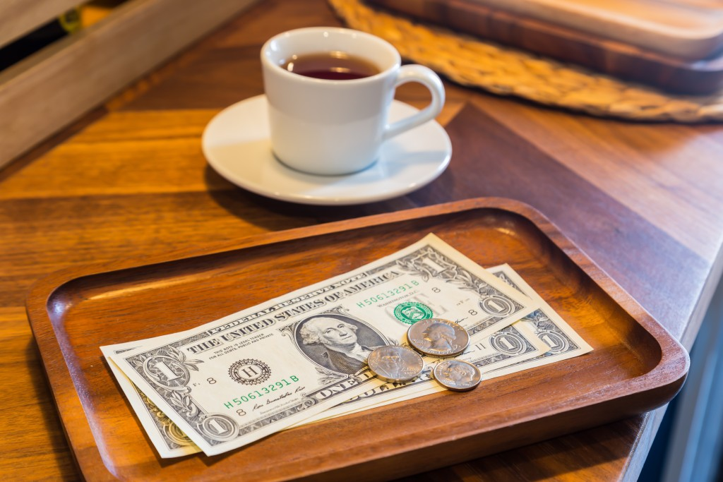 Dollar banknotes and coins, money tips.