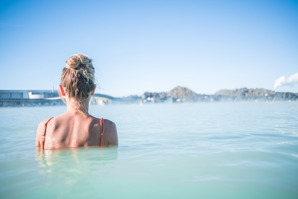Geothermal spa. Woman relaxing in hot spring pool in Iceland. Girl enjoying bathing in a blue water lagoon Icelandic tourist attraction.