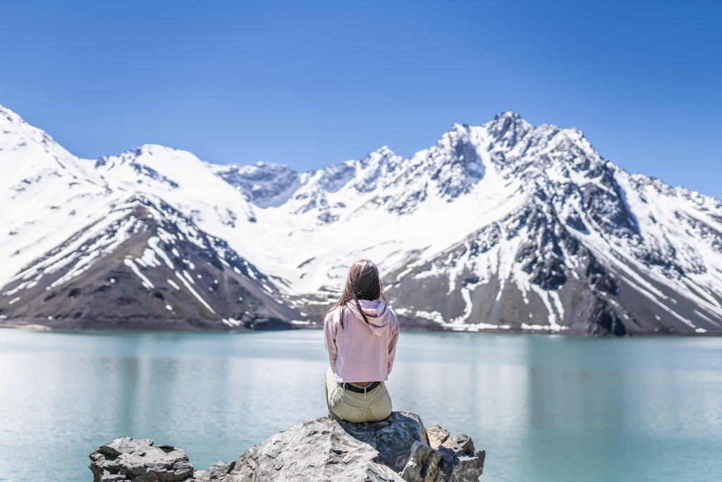 """Girl looking at the amazing mountain views of the turquoise waters from the """"Embalse del Yeso"""" (Cast Lake) close to Santiago de Chile city in Andes mountains. Snow mountains and water reflections"""