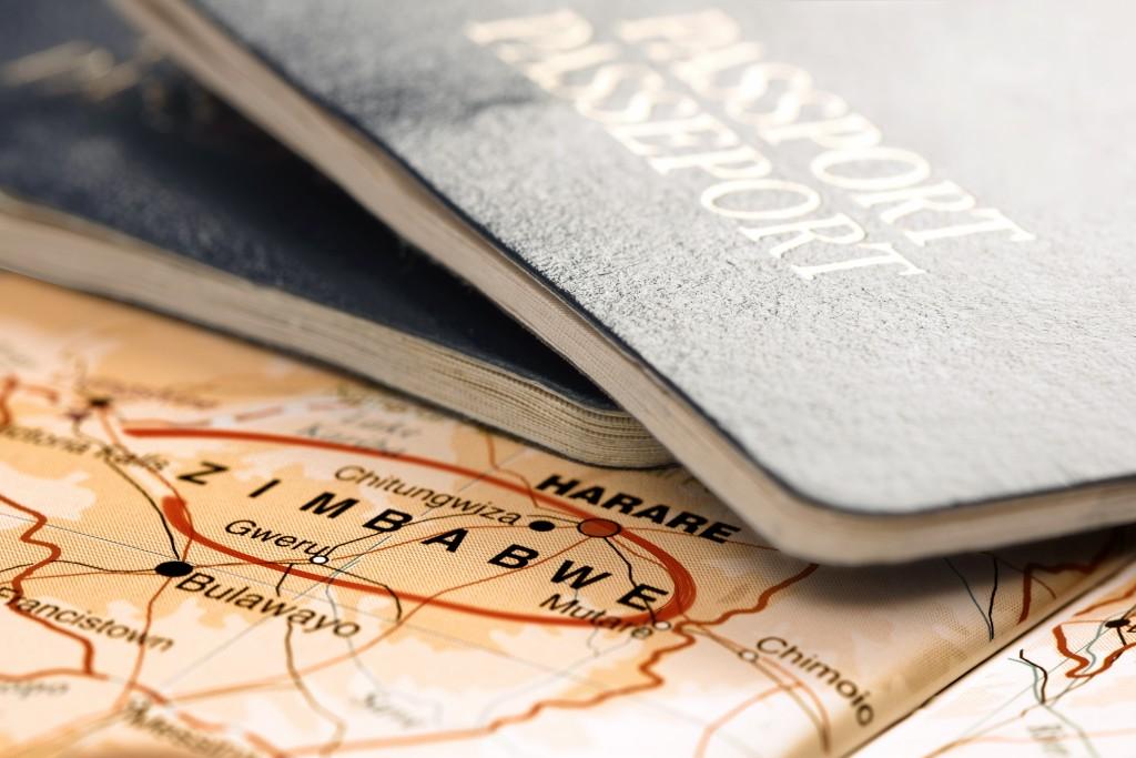 Destination Zimbabwe. Passports on the map. Travel concept.