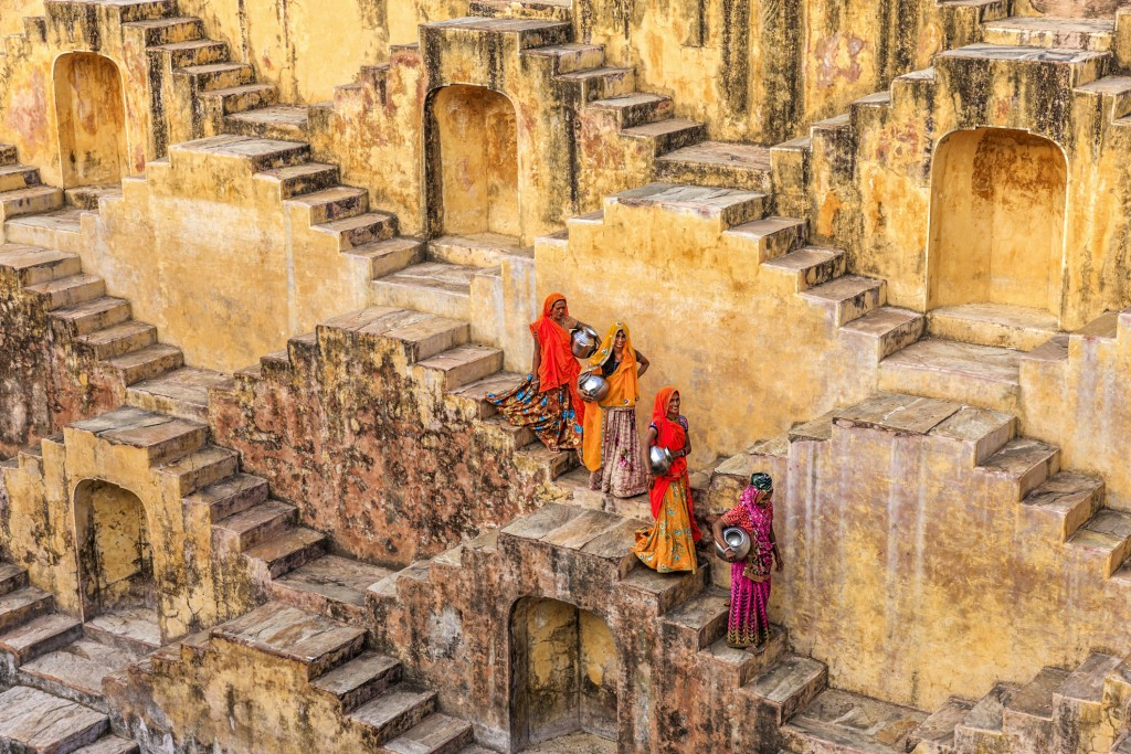 Indian women carrying water from stepwell near Jaipur, Rajasthan, India. Women and children often walk long distances to bring back jugs of water that they carry on their head.